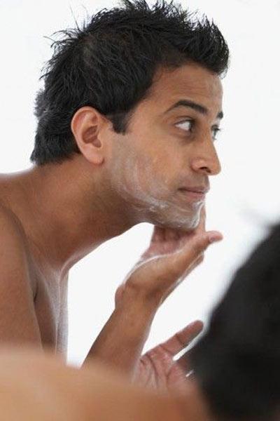 homme réalisant un gommage du visage pour préparer sa peau au rasage et avoir un beau visage