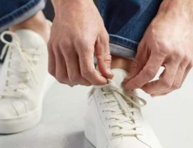 homme portant des baskets blanches