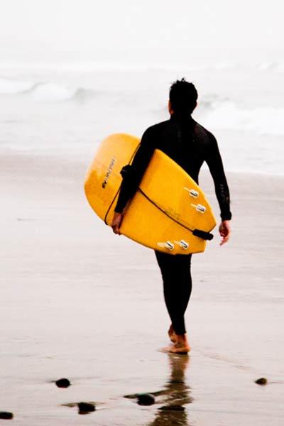 surfeur marchant sur la plage
