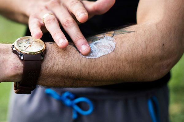 homme protégeant son tatouage du soleil